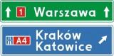 E-2f Drogowskaz tablicowy umieszczany nad jezdnią przed wjazdem na autostradę. Wskazuje na skrzyżowaniu lub bezpośrednio przed nim kierunki do miejscowości lub dzielnic miast